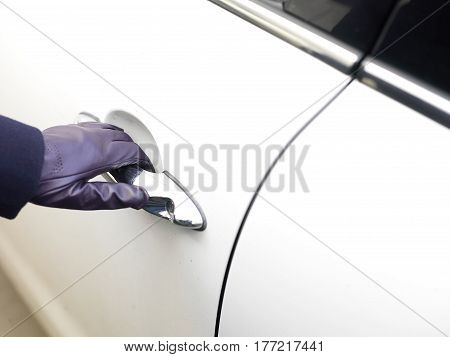 Elegant female hand wearing leather glove opening a car door cropped outdoor shot
