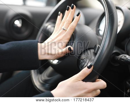 Manicured female fingers on a car horn closeup with shallow depth of field
