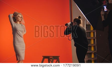 Beautiful blonde girl posing for photographer - fashion backstage, red background