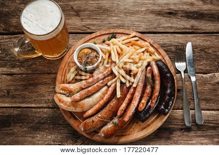 Traditional Oktoberfest menu. Mug of beer and various sausages served with sauce and french fries on wooden table, top view.