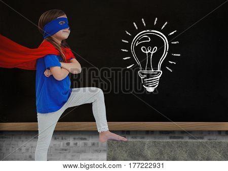 Digital composite of Super Hero kid and blackboard with lightbulb against a black background
