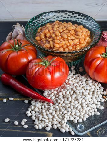 Traditional English food - baked white beans in tomato sauce and ingredients ready to cook - tomatoes dried white beans and onion