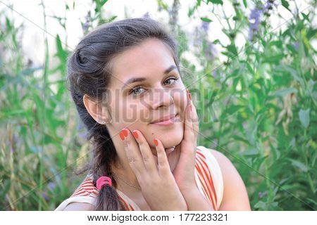 Portrait of a beautiful Russian girl on a background of blue wildflowers