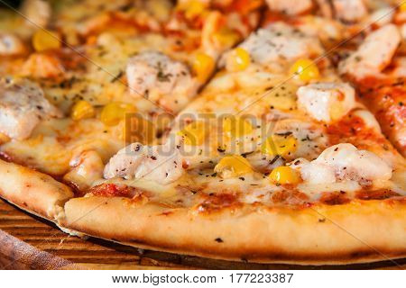 Baked italian pizza sliced and served on wooden platter, close up view. Restaurant menu photo, appetizing food background