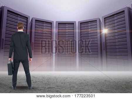 Digital composite of Businessman Standing looking at Graphic against a dark grey background