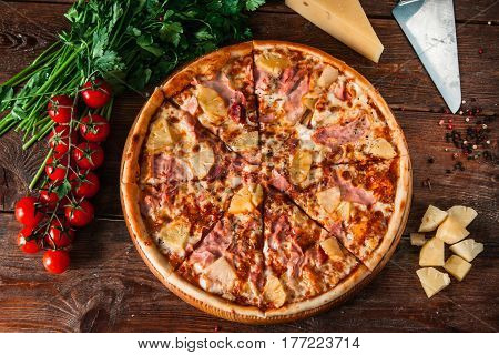 Appetizing hawaiian pizza with ham, cheese and pineapple, served on rustic wooden background with cherry, tomatoes and peppercorns, flat lay. Italian food