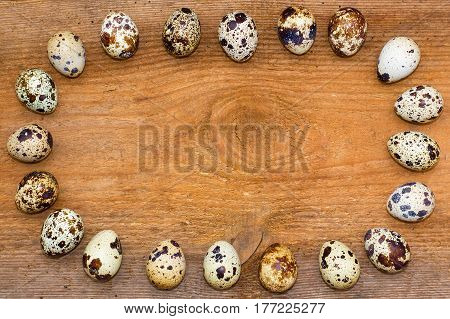 Oval Frame Made Of Quail Eggs On Old Brown Wooden Background