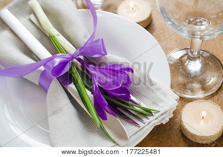 Spring Festive Table Setting With Fresh Flower and Candles. Napkin plate and cutlery on wooden table. Holidays background. Selective Focus.