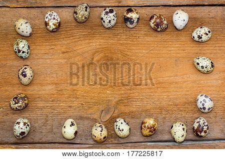 Frame Made Of Quail Eggs On Old Brown Wooden Background.