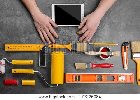 Decorator using a digital tablet. Painting roller and other tools on gray background