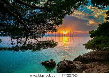 sun setting over the Adriatic sea in a small village Brela, Croatia