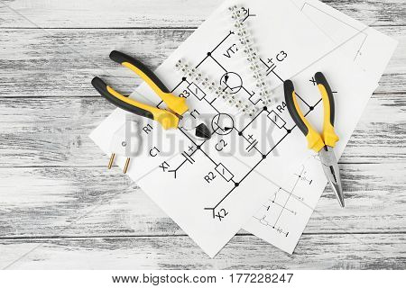 Electrician tools and schemes on wooden table