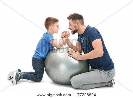 Father and son during friendly arm wrestling competition on white background