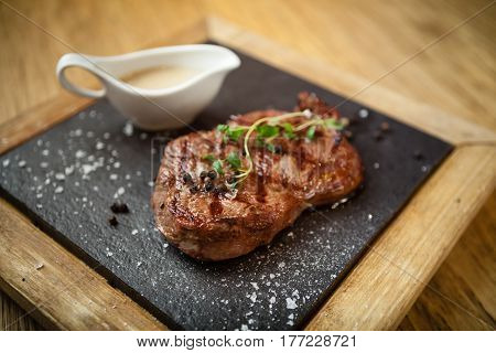 New York steak with sauce seved on a stone board