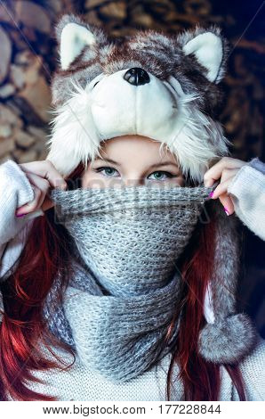 Young woman with long dyed red hair is wearing a fluffy hat with a wolf face and long pom poms is hiding her face behind her grey knitted scarf.