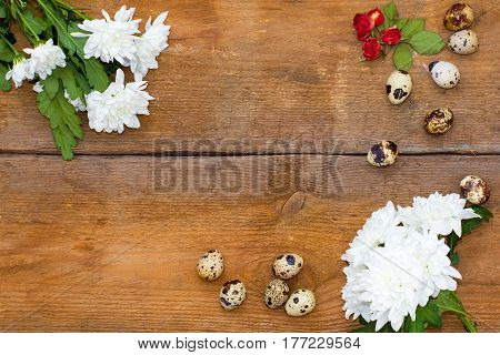 Flowers Chrysanthemums, Roses And A Few Quail Eggs On Old Brown Wooden Background.