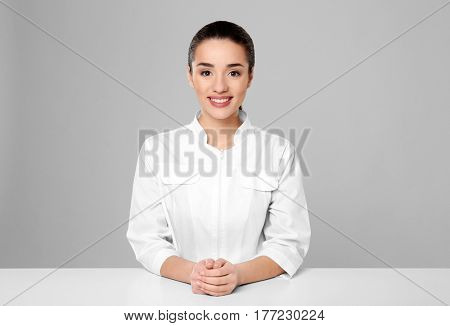 Young woman pharmacist standing at table on grey background