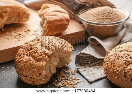 Broken buns and glass bowl of bread crumbs on grey background
