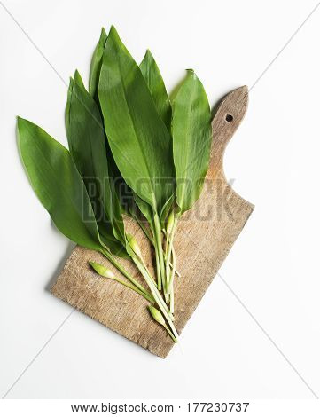 Wild garlic leafs on white background overhead shoot