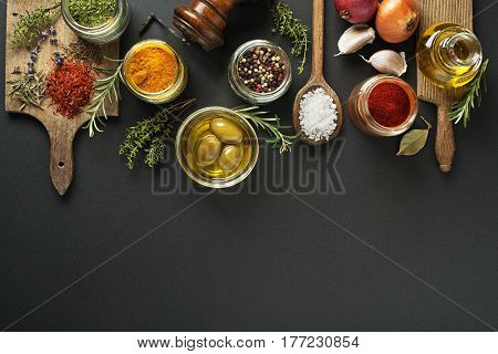 Fresh herbs and spices on a black background