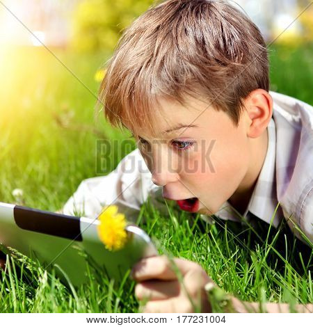 Surprised Kid with Tablet Computer on the Summer Meadow