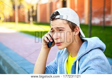 Worried Teenager with Cellphone sit on the City Street