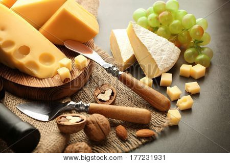 Cheeseboard with grape and nuts on grey table
