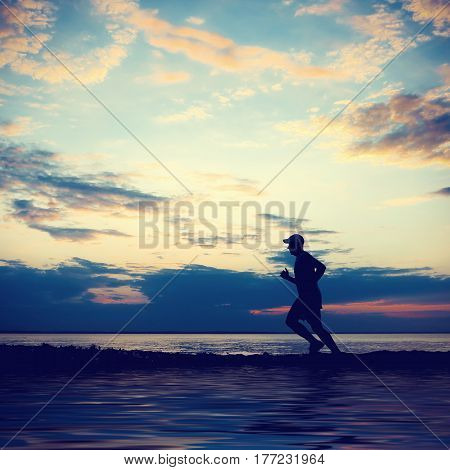 Toned Photo of Man Silhouette running on the Sunset Background