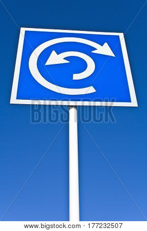 Roundabout sign over a blue clear sky