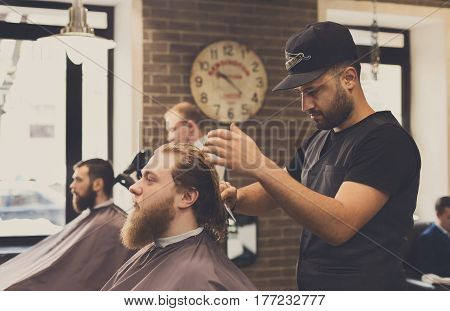 Barbers work in barbershop with bearded clients. Making modern hairstyle in male hair salon