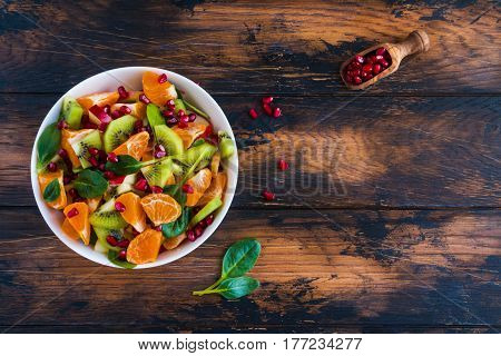 Vegetarian low-calorie salad with fresh fruits spinach and pomegranate seeds. White bowl on the wooden rustic table top view.