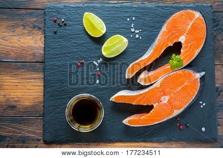 Two big raw steaks of salmon with olive oil fresh lime salt and pepper on a black stone board on the wooden table top view.