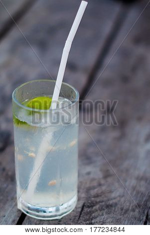 A glass of lemonade from lime and a straw on a rough wooden table. Alcohol cocktail with gin, lime and tonic on a gray wooden background.