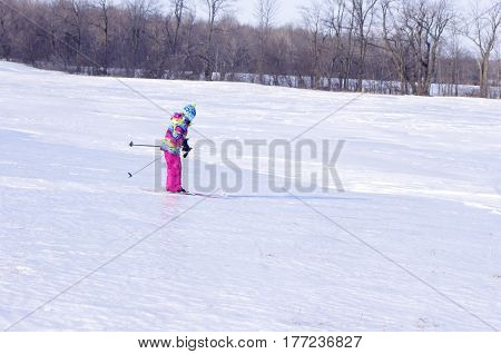 Young Girl cross country skiing  in field