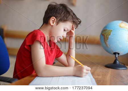 little schoolboy writing hard homework at home