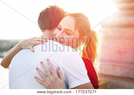 Young blonde woman embracing boyfriend outdoor in sunset