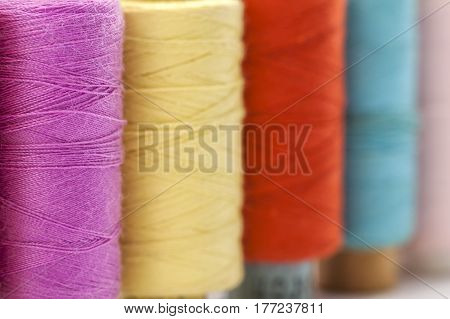 Reels or spools of multicolored sewing threads. Threads of all colors. Shallow depth of field. Close-up macro shot.