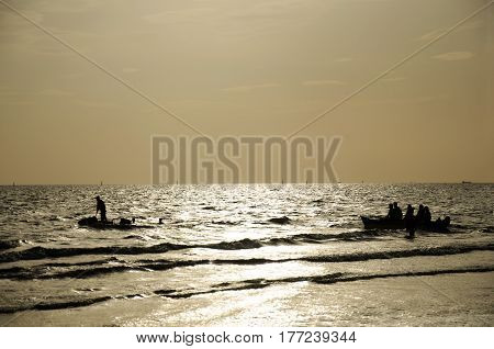 Silhouette Thai People And Traveler Travel And Playing Jetski And Banana Boat With Wave On The Sea A