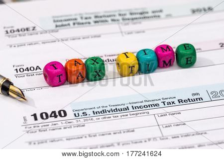 Tax Form With Wooden Cubes, Dollar Bills, Coin.