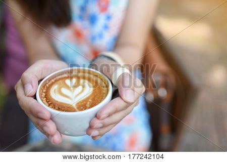 hand woman hold a cup of coffee in workplace office during morning time on monday