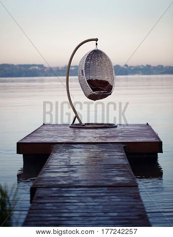 Empty egg chair on a bridge on a lake background