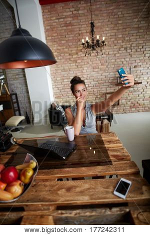 Young woman making selfie at stylish home.