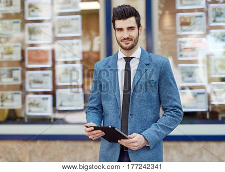 Portrait of handsome young real estate agent standing front of agency, holding tablet.