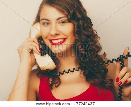 Amazed beautiful curly woman  talking on white vintage telephone isolated over white background