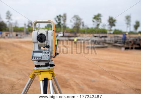 Surveyor equipment tacheometer or theodolite outdoors at construction site and construction worker in safety uniform