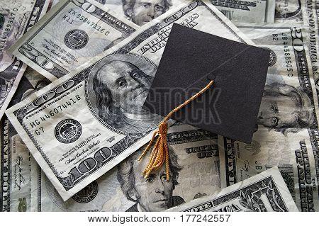 Small graduation cap on assorted cash bills
