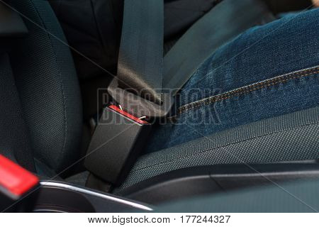 Close up of male hand fastening car safety seat belt while sitting inside of vehicle before driving