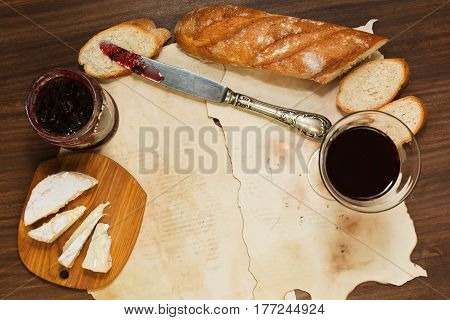 Lunch or breakfast with a glass of red wine fresh baguette bread brie or camembert cheese and cowberry jam served on vintage styled wooden table and blank old paper sheets