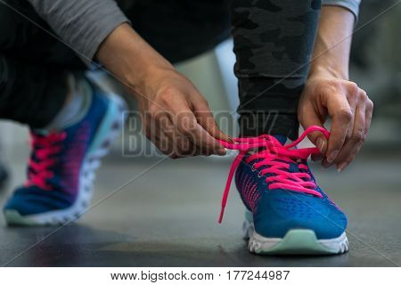 Running shoes - woman tying shoe laces. Closeup of fitness woman getting ready for engage in the gym