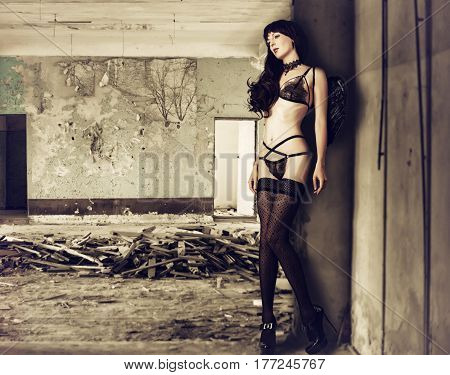 beautiful slim young woman model wearing black lace lingerie - bra panties stockings and angel wings into abandoned house